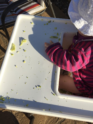 Shot from above of a white high chair tray covered in small pieces of broccoli and a baby sitting in the highchair