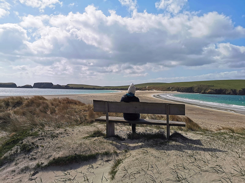 on a bench overlooking St Ninian's Isle