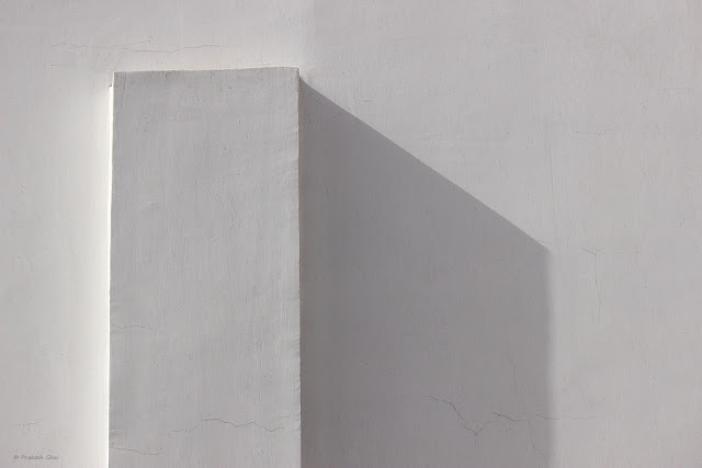 A Minimalist Photo of a White Indian Wall using simple geometric shapes and light and shadow.