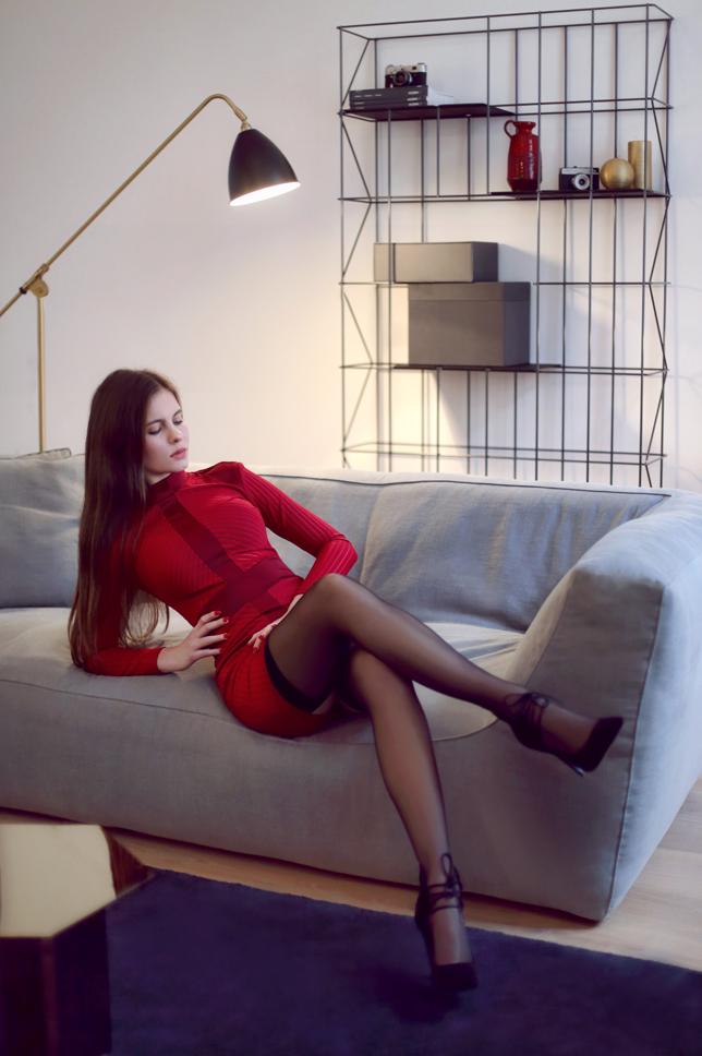 Czerwona obcisła sukienka, pończochy i sznurowane botki na szpilce