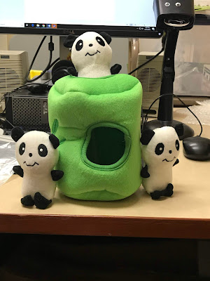 3 stuffed pandas and a green container