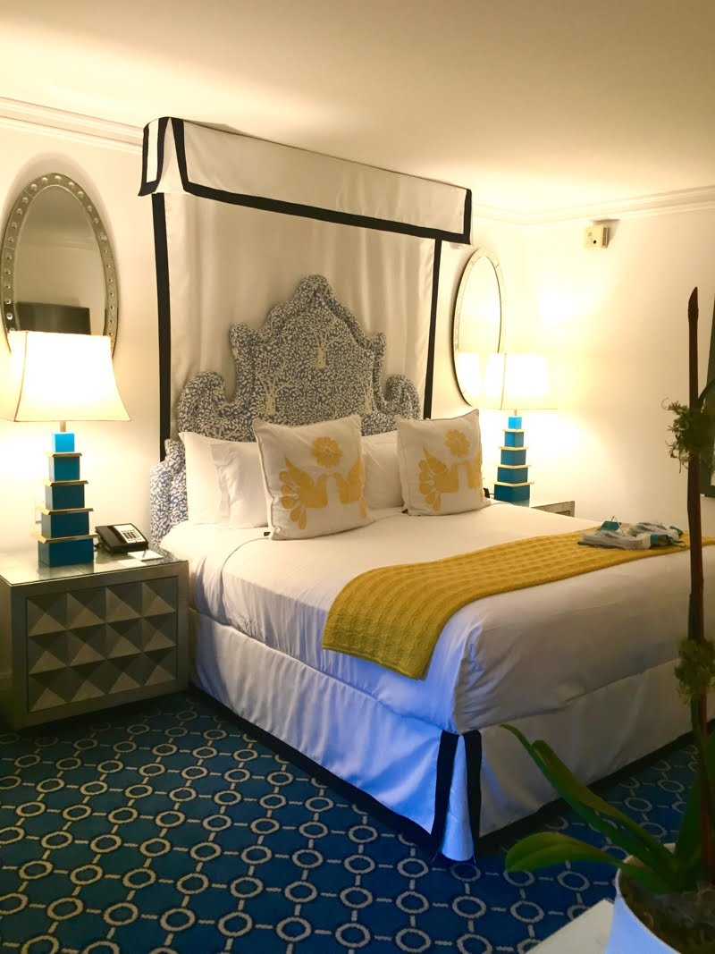 Hotel bed room with blue decor and yellow and white bedding.