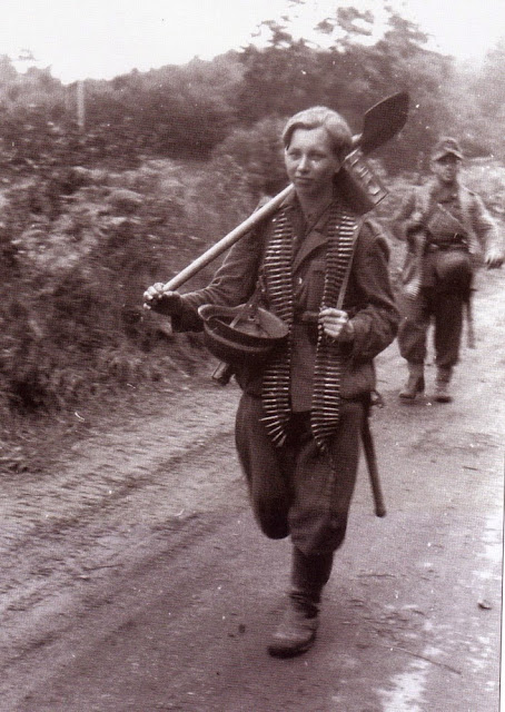Child carrying shovel and machine gun rounds worldwartwo.filminspector.com