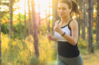 an image showing a woman running with a phone in one hand and earphones plugged in