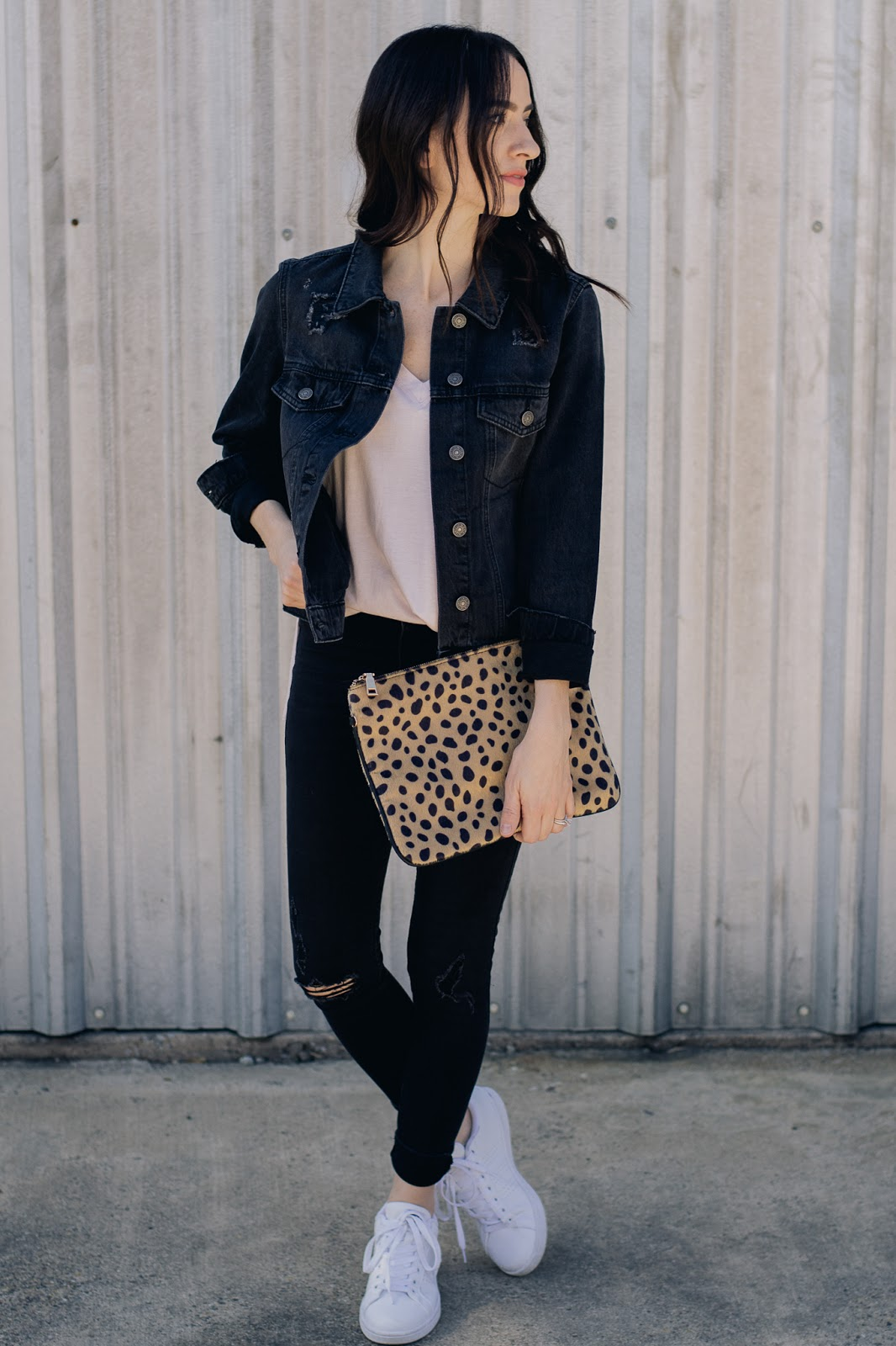 Casual weekend style in black distressed denim jacket and white sneakers