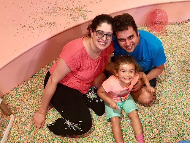 A family of three pose smiling for a photo in a pool full of colorful sprinkles