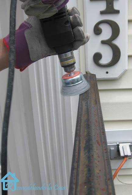 using a wire brush drill attachment to clean railing rust