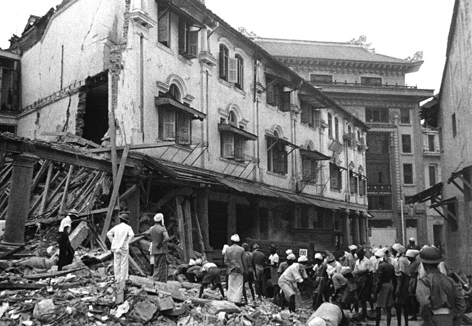 Workmen clear up raid debris in Singapore on January 17, 1942, after a Japanese bombing raid on the British naval base.