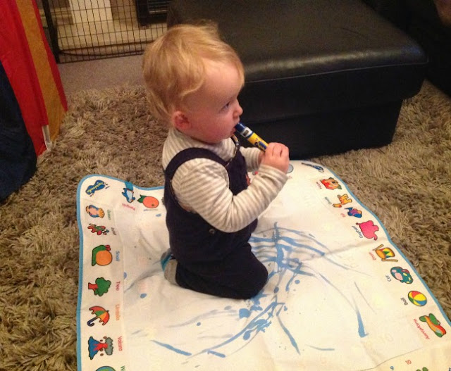 toddler sat on aquadoodle eating pen
