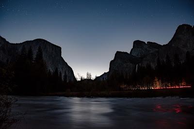 Lago de noche con montañas y bosque luminoso de fondo