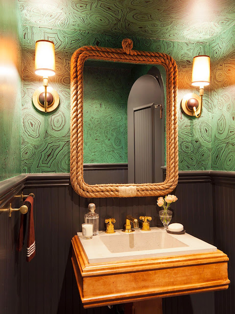 powder room with malachite inspired wallpaper, mirror with rope frame and matching gold wall mounted lamps