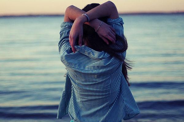 mulher de costas olhando para o mar e pensando na vida