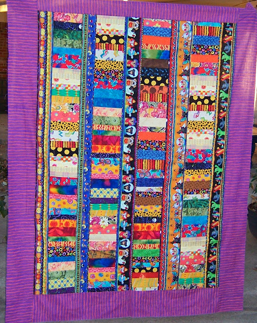Striped Halloween fabric forms sashing between columns of colorful coins to create this happy quilt.