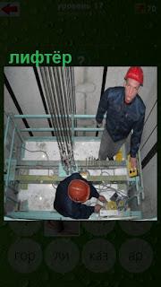 лифтеры находятся в шахте где ходят лифты и работают в касках
