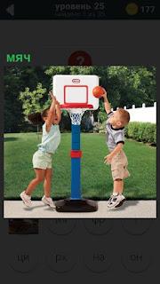 Играют в баскетбол мячом дети, забрасывая его в корзинку