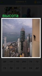 На большой высоте дома стоит мужчина на парапете