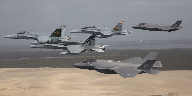 Image Attribute: Royal Australian Air Force F/A-18 Hornets fly in formation with a pair of F-35A Joint Strike Fighters over Stockton Beach, NSW. (Before landing at Williamtown AFB) / Source: Australian Defence Force