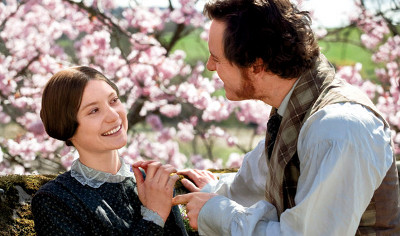 Michael Fassbender and Mia Wasikowska from Jane Eyre 2011. Both laugh as they tussle for something in Jane's hand.