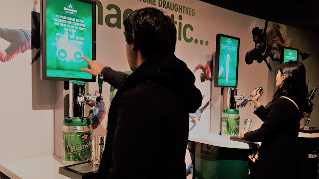 Tourists tapping a beer at Heineken Experience