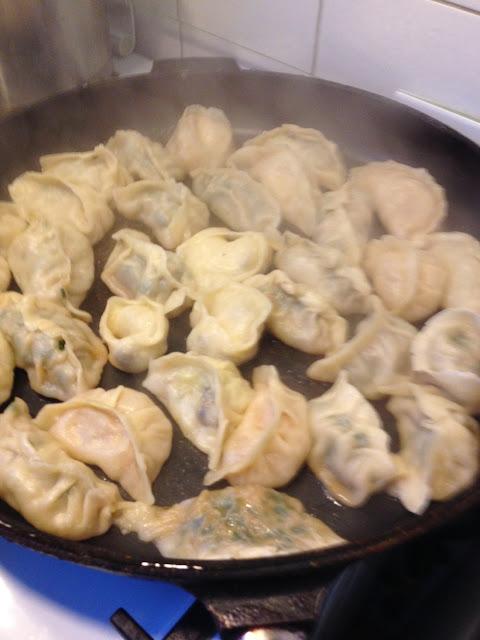 Koekenpan met dumplings die liggen te bakken.