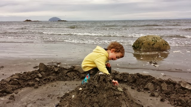 toddler building sandcastles