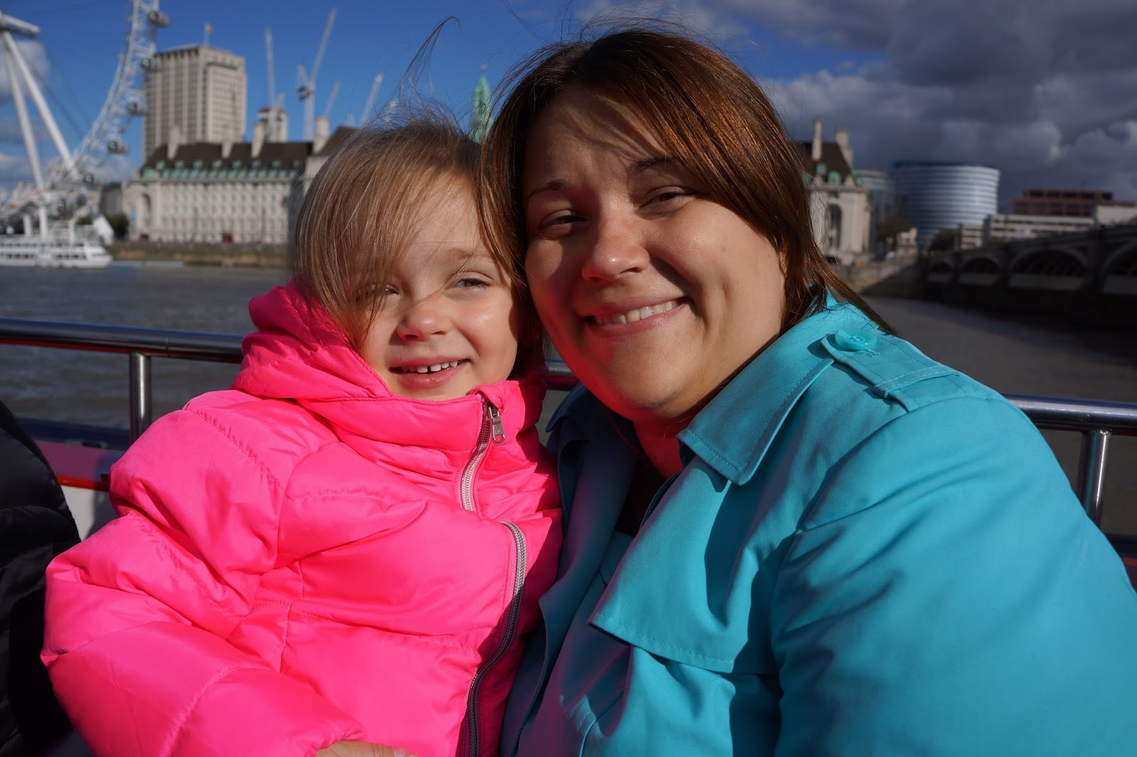 mum and daughter wearing bright jackets at westminster pier