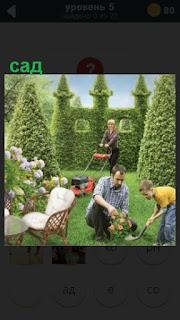 отец с ребенком в саду сажает цветы а мама косит траву