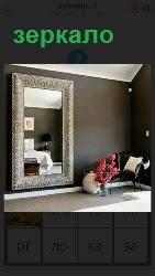 в комнате на стене висит большое зеркало и букет цветов стоит в вазе