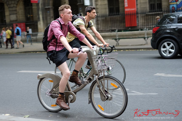 Two men commuting by bike, one in long sleeve shirt, shorts and boots. Paris photos by Kent Johnson for Street Fashion Sydney.