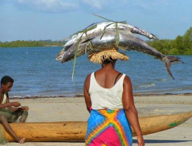 Funny African woman carrying fish on her head picture
