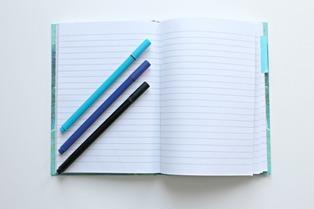 quaderno a righe con penne blu e nere