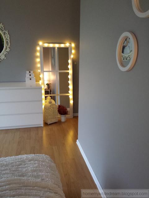lustro w ramie okiennej, białe lustro, szara sypialnia, lampki gwiazdki