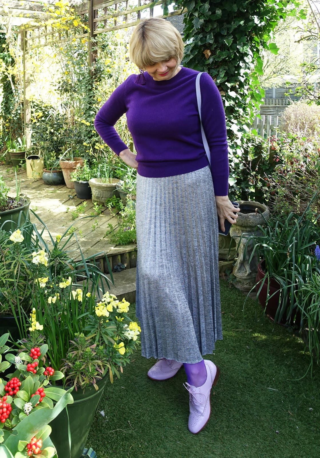 Lilac brogue shoes worn with a long metallic pleated skirt, purple tights and cashmere jumper and lilac bag.