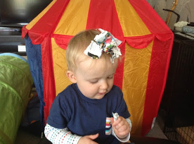 picture of baby sitting with scraps of paper on their head