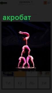 Выполнена акробатическая фигура акробатом в виде одного над другим. Верхний с поднятыми ногами