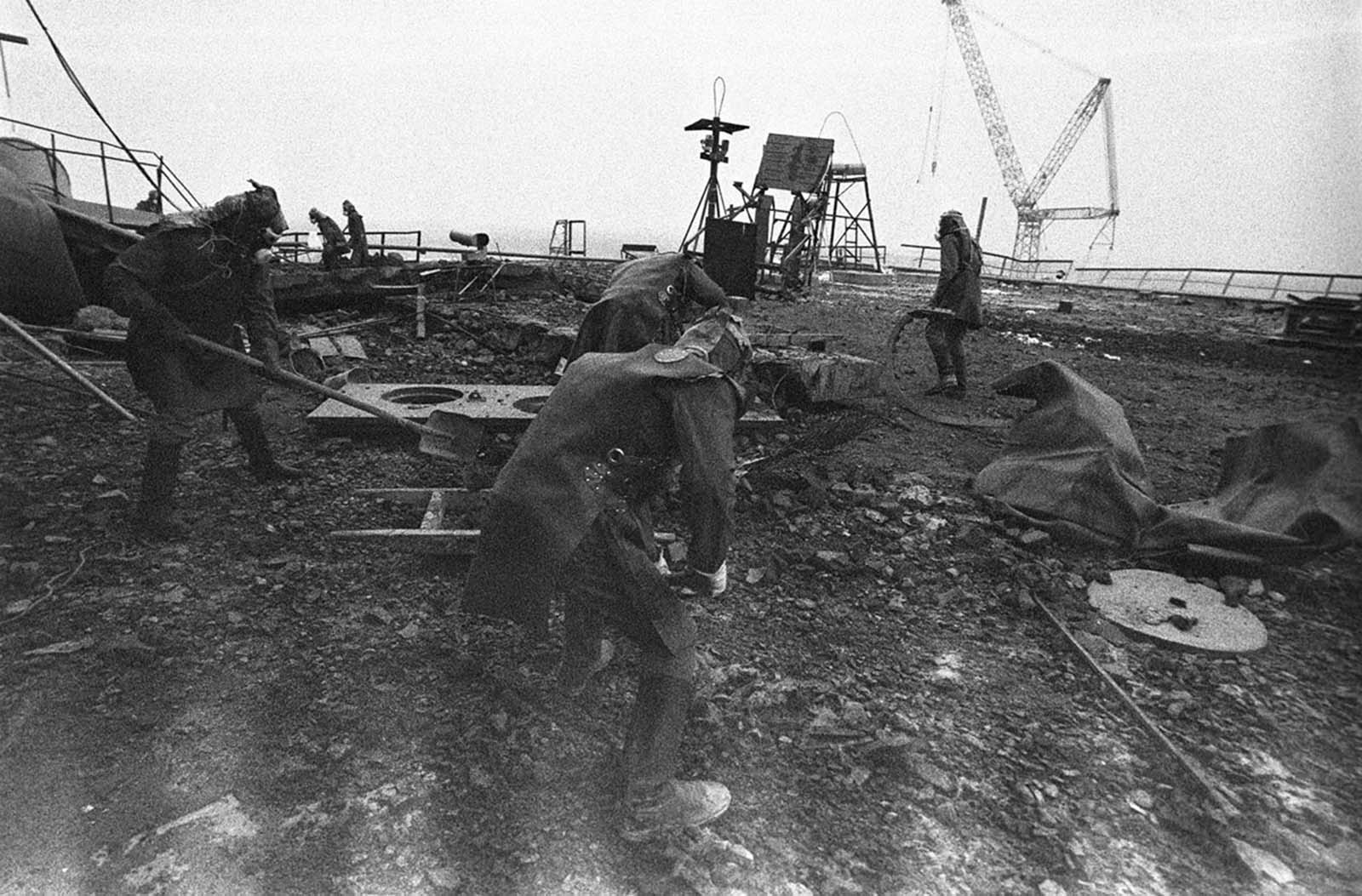 Liquidators clean the roof of the No. 3 reactor. At first, workers tried clearing the radioactive debris from the roof using West German, Japanese, and Russian robots, but the machines could not cope with the extreme radiation levels so authorities decided to use humans. In some areas, workers could not stay any longer than 40 seconds before the radiation they received reached the maximum authorized dose a human being should receive in his entire life.