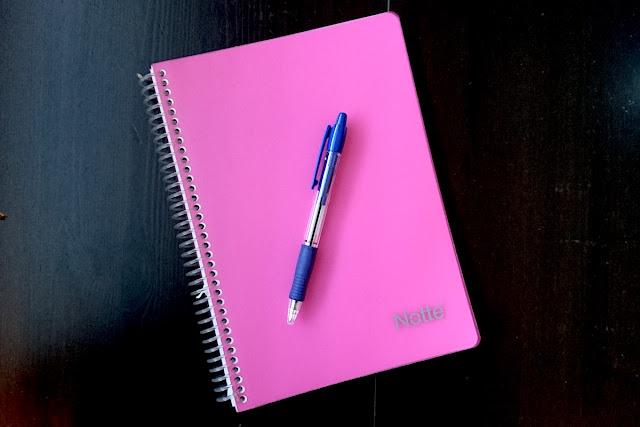 Pinkki muistivihko ja kynä päiväkirjan kirjoittamista varten