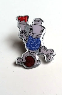 The enamel pin depicting the mascot of Maker Faire Adelaie, Sam Robot who is holding a paintbrush with red paint above his head with his right hand and a spanner in his left.