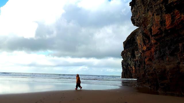 Lapsi rannalla, kallioseinä, hiekkaranta, meri, pilvinen taivas, ballybunion