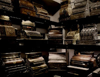 A room full of different vintage cash registers.