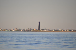 view of light house tower and seaside town across the water