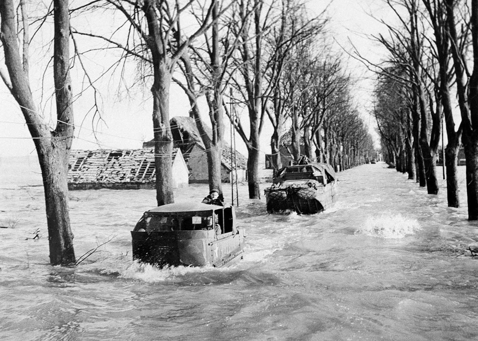 A party sets out to repair telephone lines on the main road in Kranenburg on February 22, 1945, amid four-foot deep floods caused by the bursting of Dikes by the retreating Germans. During the floods, British troops further into Germany have had their supplies brought by amphibious vehicles.