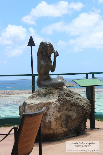 A statue of a mermaid facing Tumon Bay at Reef Hotel