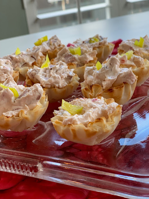 Cream cheese appetizers in pastry cups with little pieces of pepperoncini on top