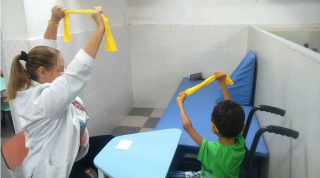 Imagem mostra a Fisioterapeuta e o paciente em exercício com os braços.