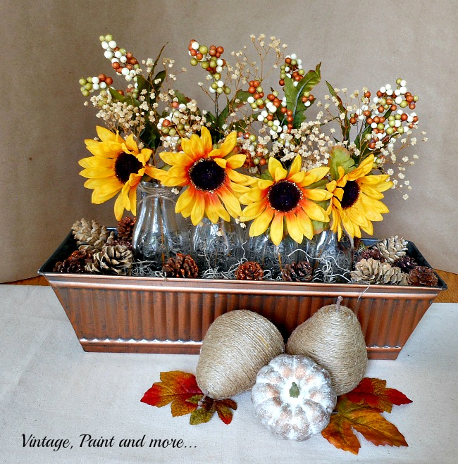 Vintage, Paint and more... centerpiece done with sunflowers in milk bottles in a copper basket with pinecones for fall