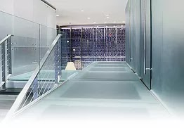 Laminated glass flooring is produced by bonding two or more layers of heat treated pressured glass together with a plastic resin