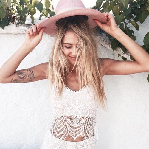 Rubia con sombrero , rie, lleva tatuaje en el brazo