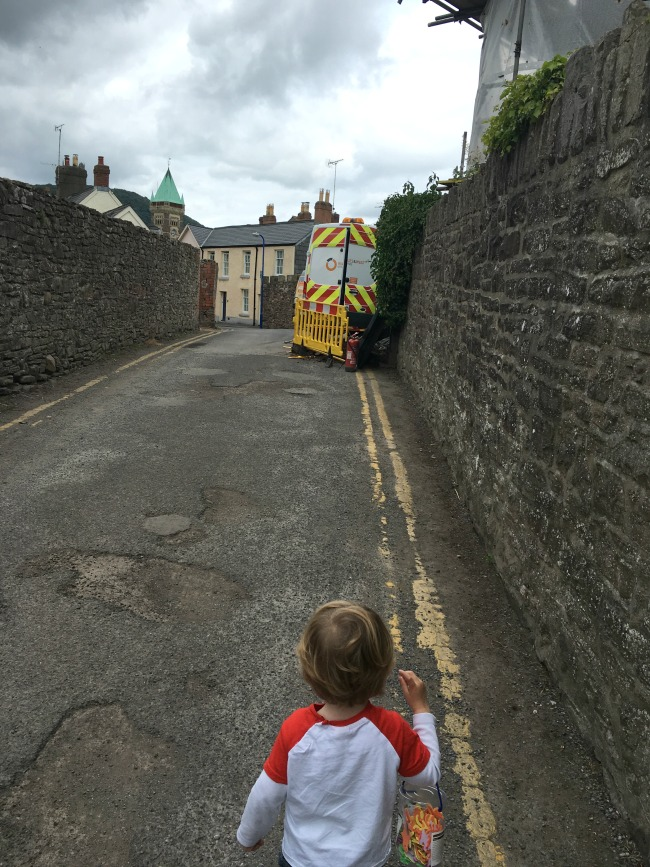 Abergavenny-castle-walls-and-a-toddler-carrying-a-bag-full-of-stickers-on-road-with-yellow-lines-and-a-van-parked