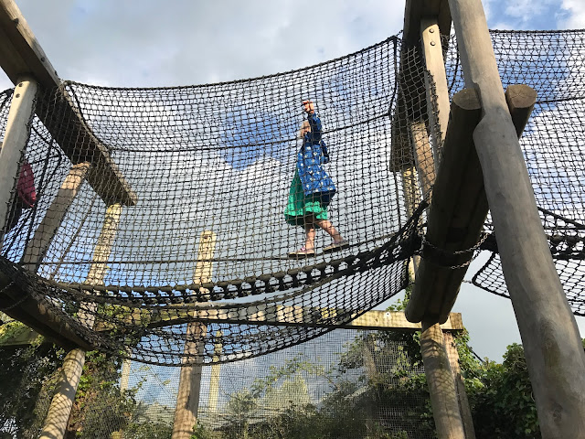 A highup walkway surrounded by netting with a girl walking across a tightrope. An animal enclosure is in the background